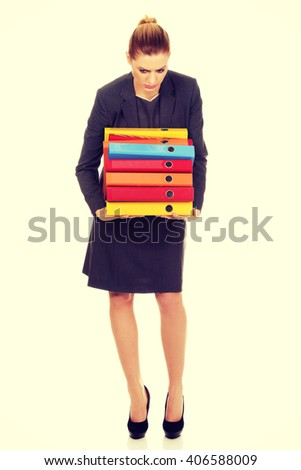 Young business woman carries heavy binders - stock photo