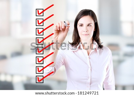 Young business woman checking on checklist boxes. Office background.