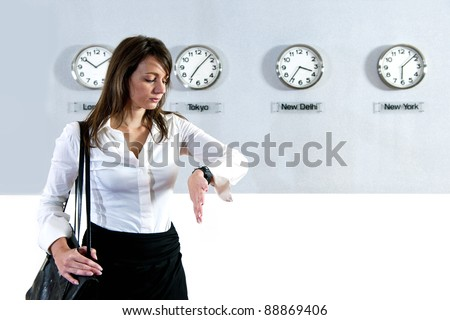 Young business woman checking the time on her watch with various international clocks, displaying world time, in the background - stock photo