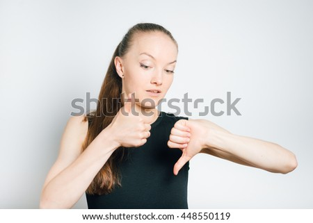 Young business woman chooses good or bad, isolated on a gray background