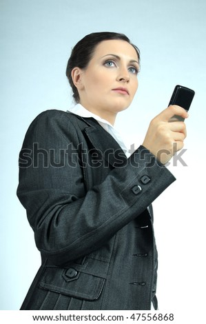 Young business woman, concentrated looking forward, holding a business model cell phone . - stock photo