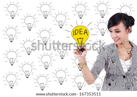 Young business woman drawing light bulb with chalk on whiteboard - stock photo
