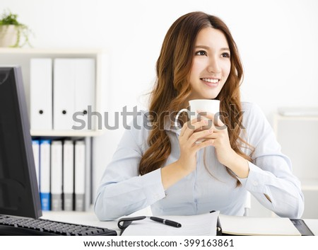 Young business woman drinking coffee and looking - stock photo