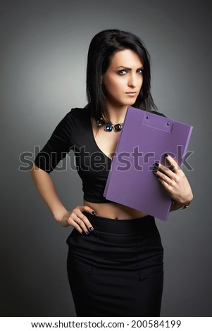 Young business woman, elegantly dressed focuses on the subject, with a clipboard under her chin. Gray background. - stock photo