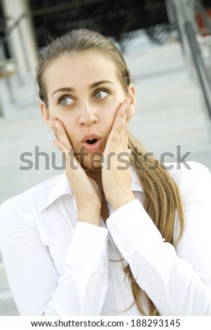 Young business woman expressed surprise. His hands are on her cheeks - stock photo