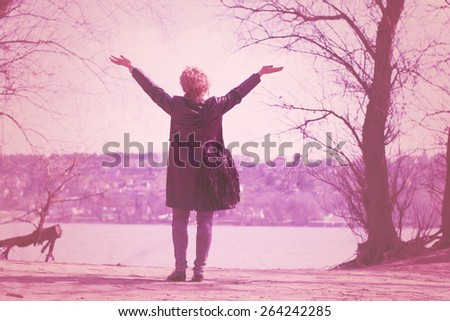 Young business woman having a launch break on the beach by the river. Enjoying sun and free time with arms above herself. - stock photo