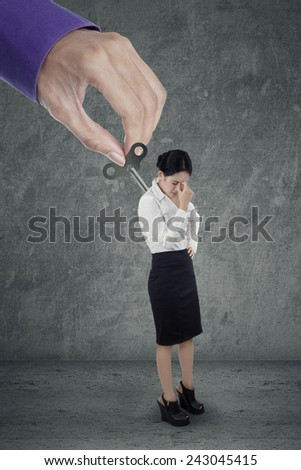 Young business woman having headache after overwork controlled by hand - stock photo
