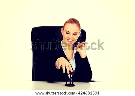 Young business woman holding a hourglass - stock photo