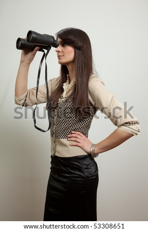 Young business woman holding and looking through binoculars. Isolated on white - stock photo