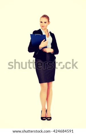 Young business woman holding clipboard - stock photo