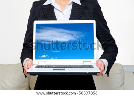 Young business woman holding laptop with blue sky on screen