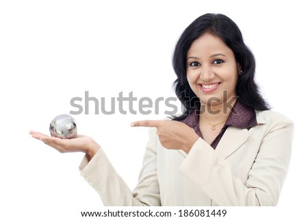 Young business woman holding puzzle globe against white