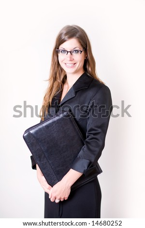 Young business woman holds her leather portfolio in her arm. She looks as if she is off to a business meeting. She is dressed in modern clothing.