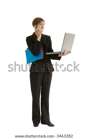 Young business woman in a tailored suit holding computer, cell phone, and folders. Image is isolated on a white background. - stock photo