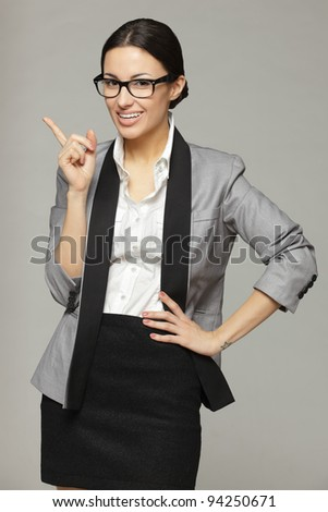 Young business woman in eyeglasses pointing at copy space, over grey background