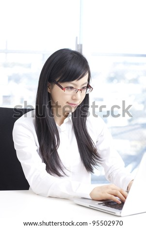 Young business woman in glasses working on laptop computer - stock photo