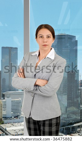Young business woman in her office overseeing the city skyline. - stock photo