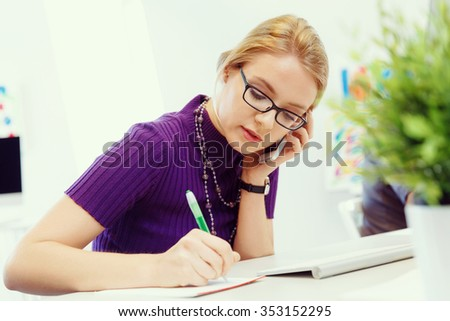 Young business woman in office holding mobile phone - stock photo