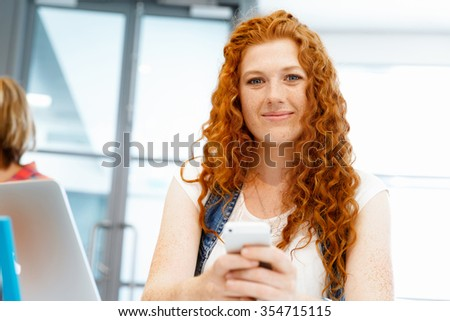Young business woman in office holding mobile phone