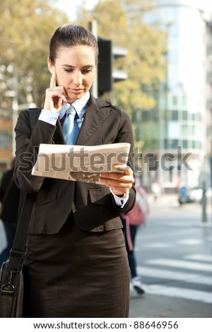 Young business woman in suit reading a newspaper, outdoor - stock photo
