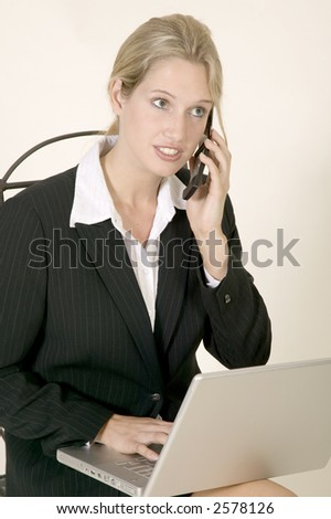 Young business woman in suit sitting down whilst working with her laptop computer in her lap and talking on the telephone