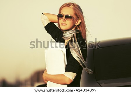 Young business woman in sunglasses next to her car. Female blond fashion model outdoor - stock photo