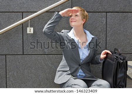 Young business woman in the city on stairs looking into the distance - stock photo