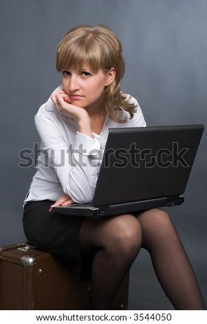 young business woman in white shirt and black skirt sitting on big suitcase with notebook on her knees - stock photo