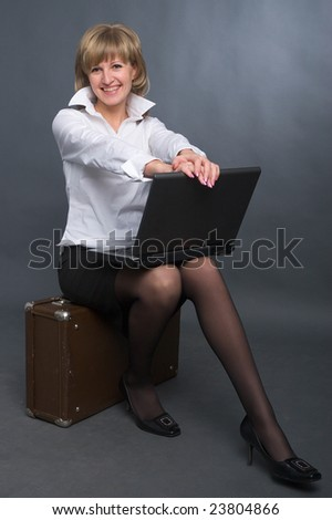 young business woman in white shirt and black skirt sitting on suitcase with notebook on her knees on grey background - stock photo