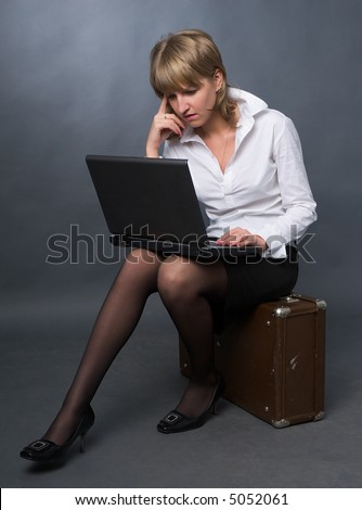 young business woman in white shirt and black skirt sitting on suitcase with notebook on her knees - stock photo