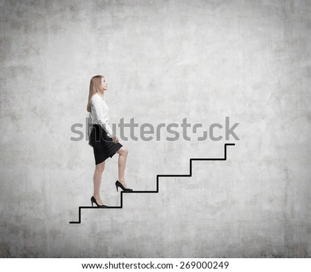 Young business woman is going up to the stairs. A concept of successful business project - stock photo