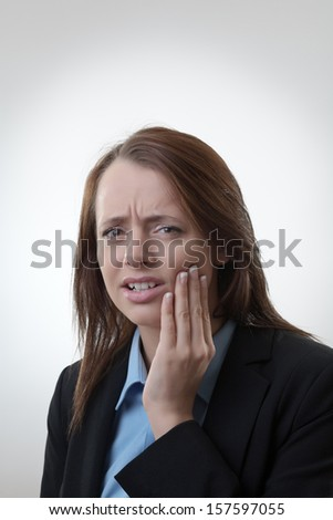 Young business woman is having a toothache - stock photo