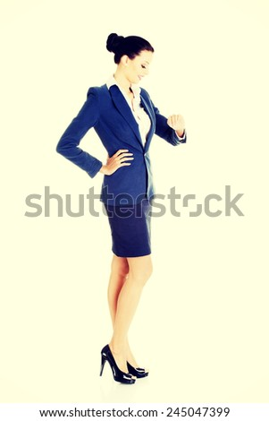 Young business woman is looking at her watch on wrist.  - stock photo