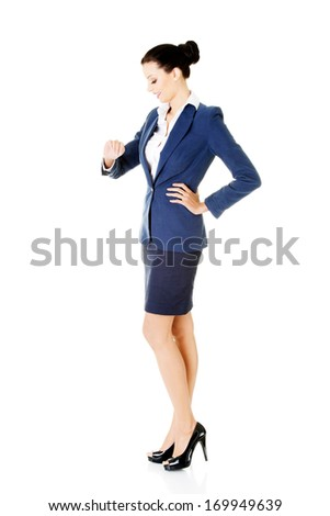 Young business woman is looking at her watch on wrist. Isolated on white. - stock photo