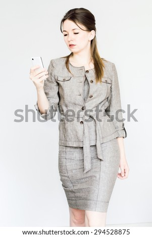 Young business woman is walking in office dress and looking at her smart-phone - stock photo