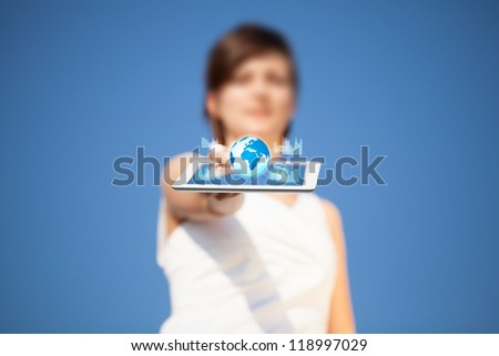 Young business woman looking at modern tablet with abstract lights and globe - stock photo