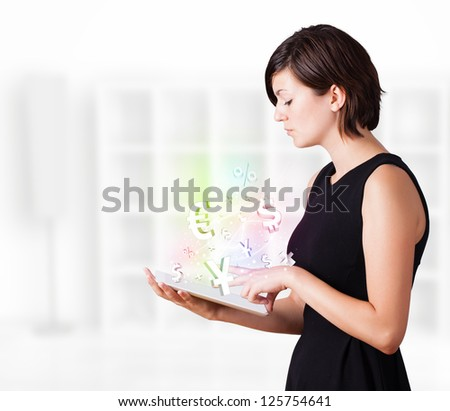 Young business woman looking at modern tablet with currency icons - stock photo