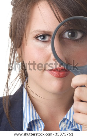 Young business woman looking at the camera through a magnifying glass, one eye magnified; close-up; isolated on a white background. - stock photo