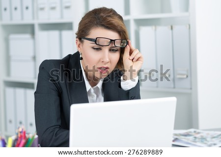Young business woman looking intently at laptop monitor seeing something strange