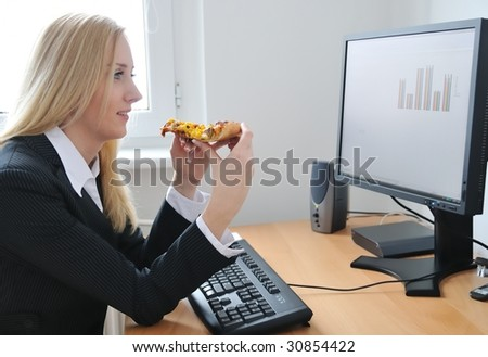 Young business woman looking on monitor and eating pizza