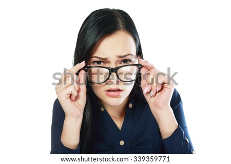 young business woman looking over glasses worry about somthing or trying to see - stock photo