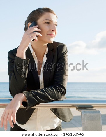 Young business woman making a phone call on her smart phone while leaning on a metallic banister near the sea during a sunny day with a blue sky, smiling and relaxed. - stock photo