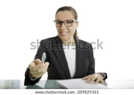 young business woman offering a pen to sign a document sitting on a desk - focus on the pen - stock photo