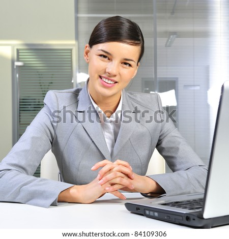 Young business woman on a laptop at her office - stock photo