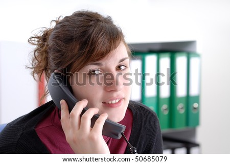 young business woman on the phone in her office with green files in the background - stock photo