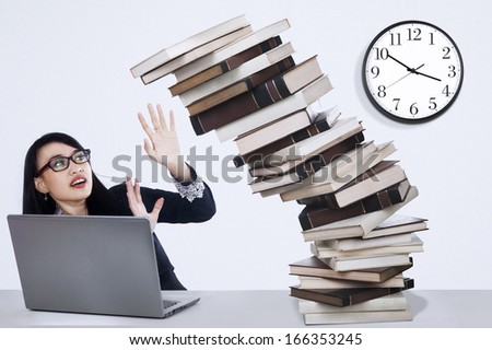 Young business woman overworked with stack of books at desk - stock photo
