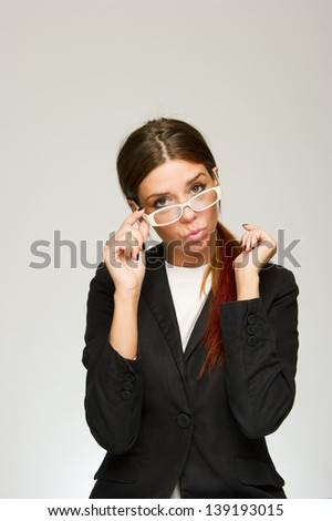 Young business woman playing with her glasses on white background