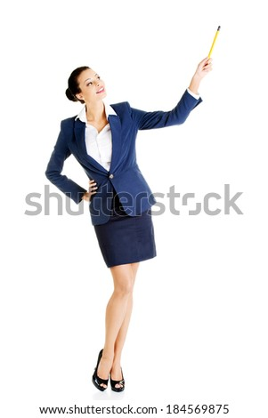 Young business woman pointing up with pen. Isolated on white.