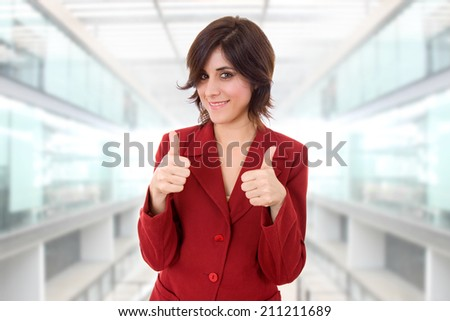 young business woman portrait going thumbs up, at the office - stock photo