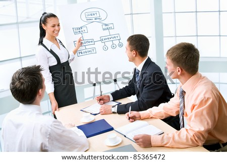 Young business woman presenting his ideas on whiteboard to colleagues - stock photo